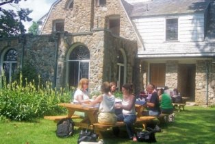 Image of students at picnic tables behind the Stone House.