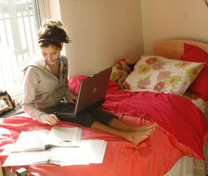 girl sitting on bed amongst papers