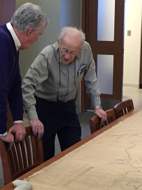 Nate Hamilton and Dr. Osher talking over a large 1910 map of Moosehead Lake