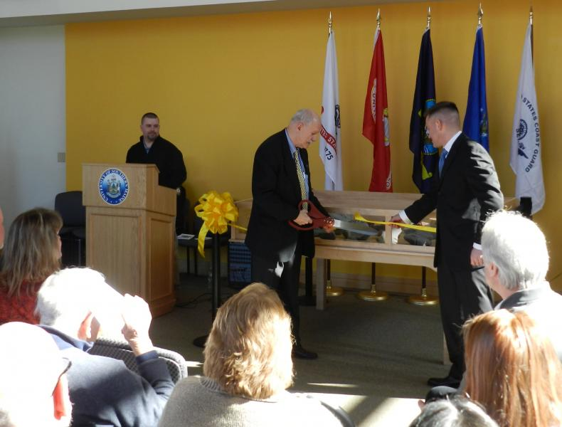 Photo of USM president David Flanagan and David Cote cutting ribbon for memorial display case