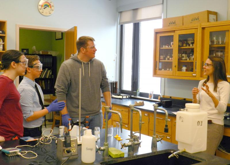 Lucille Bennedict speaking with USM and PHS students while working on a lab