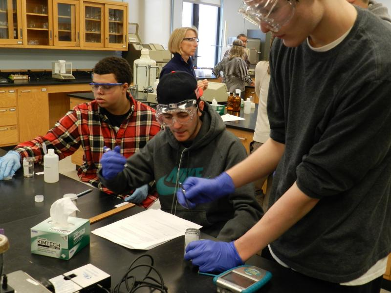 Three Portland High School students work on lab at USM