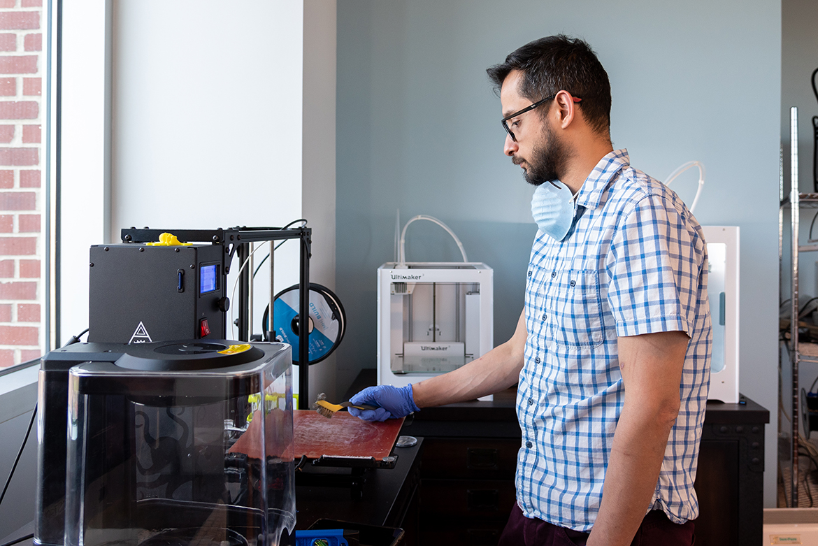 Dr. Asheesh Lanba monitors a 3D printer in USM's MIST lab as a face shield prototype materializes.