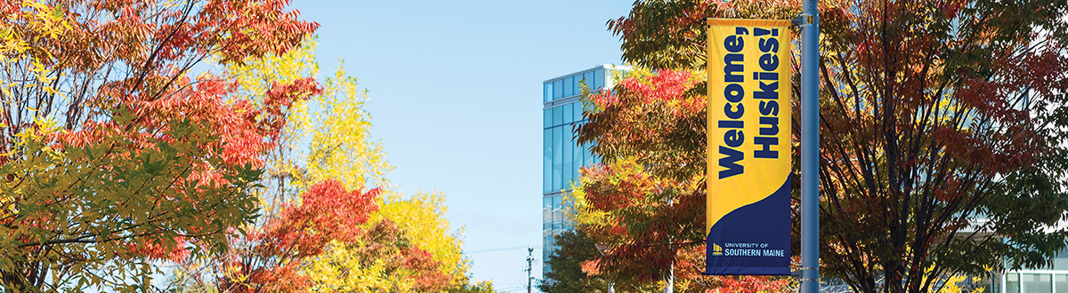 A view of colorful treetops looking down Bedford Street with the Glickman Library in the background. A banner hanging on a lamppost reads 'Welcome Huskies' above the USM logo.