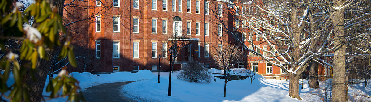 Robie-Andrews Hall, on our Gorham campus, surrounded by snow and snow-coated trees on a sunny winter day post-snowfall.