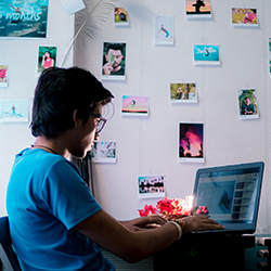A student working on a laptop surrounded by photos taped to the wall.