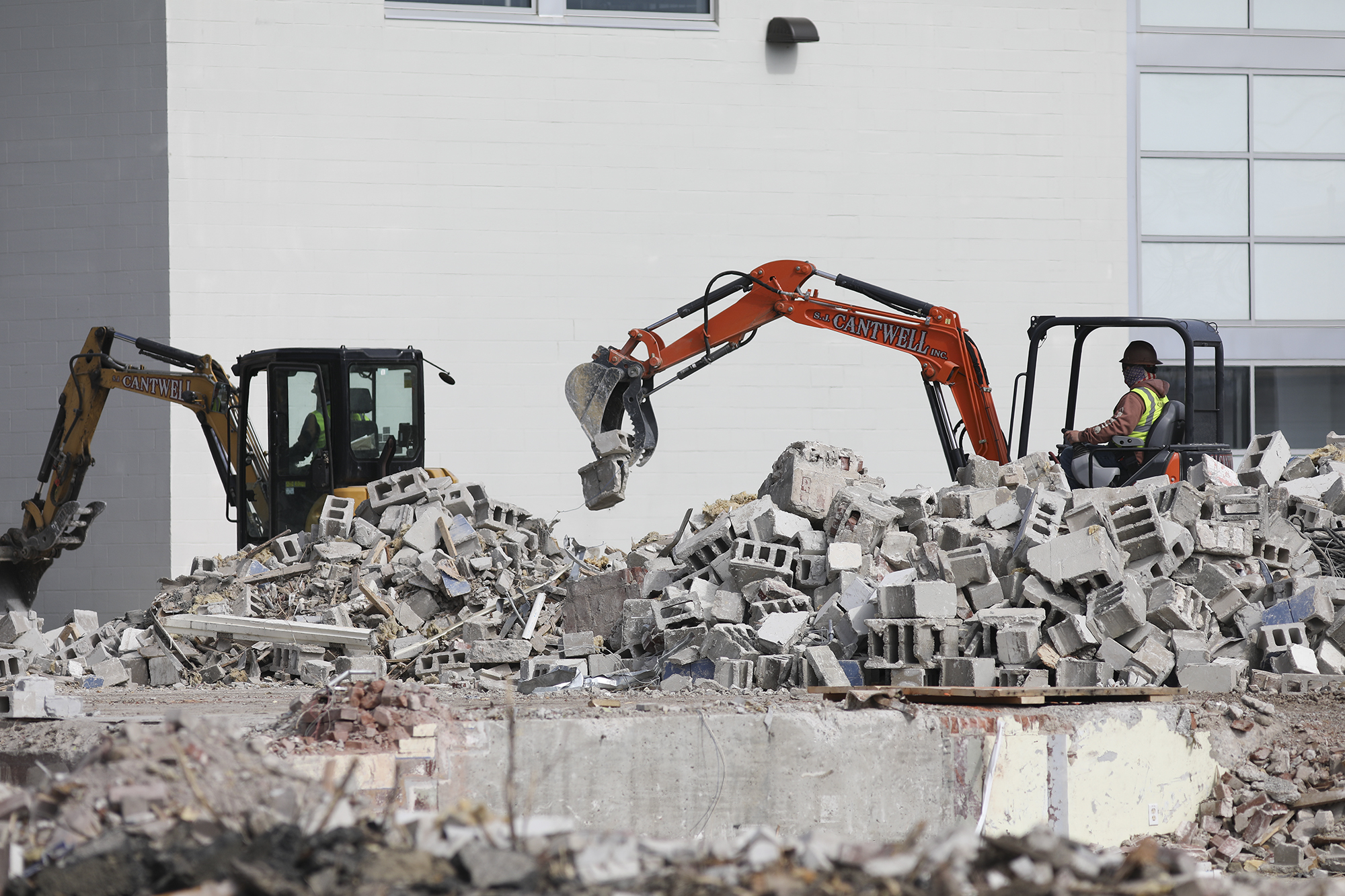 A photo of bucket loaders picking cinder blocks for recycling.