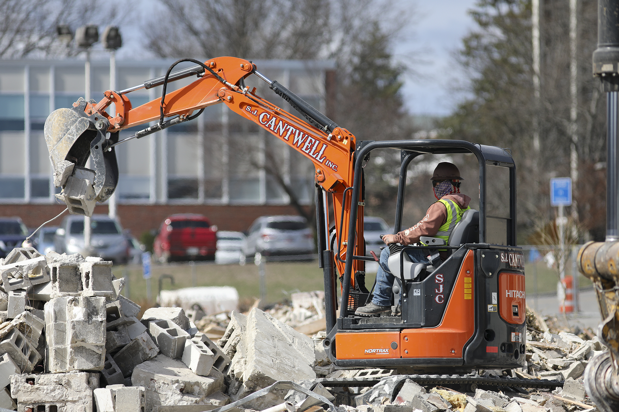 A photo of a smaller backhoe picking cinderblocks for recycling at the construction site.