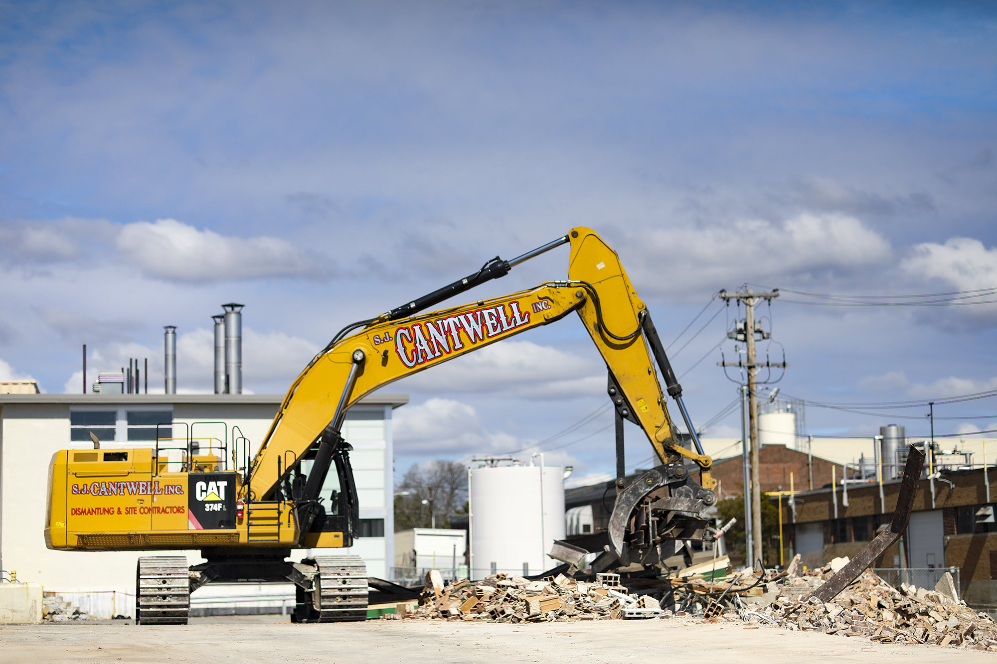 A photo of a large excavator with demolition claw attachment gathering metal for recycling