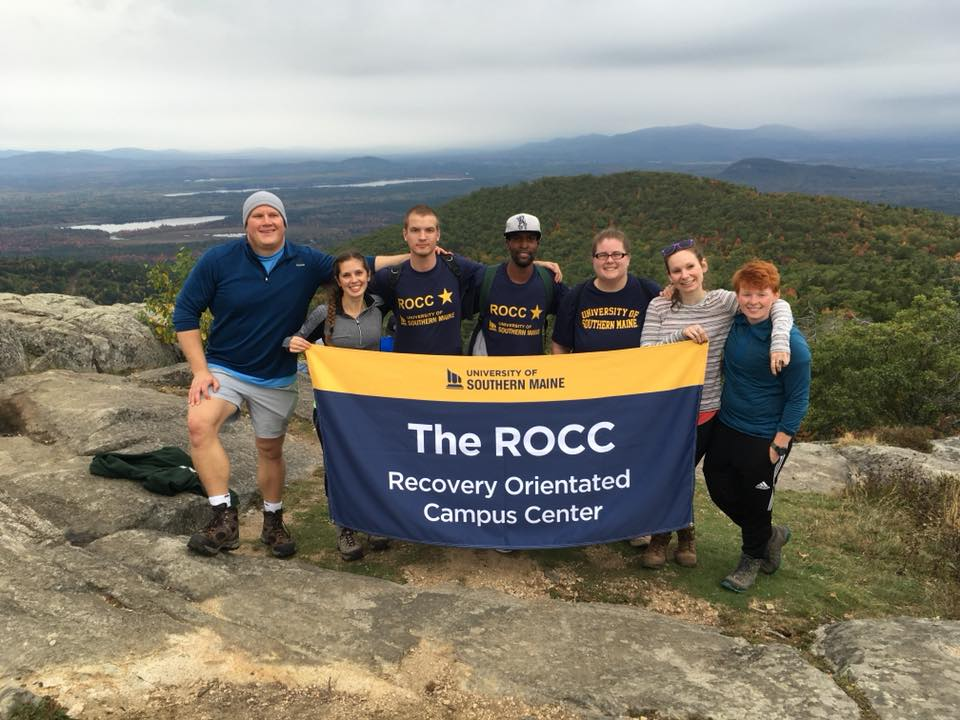 Group of ROCC peers on the top of Pleasant Mountain with ROCC banner