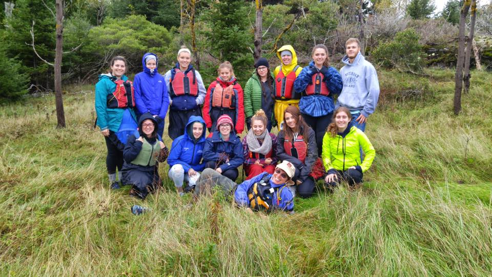 Students and faculty in a field with life jackets and outdoor gear.