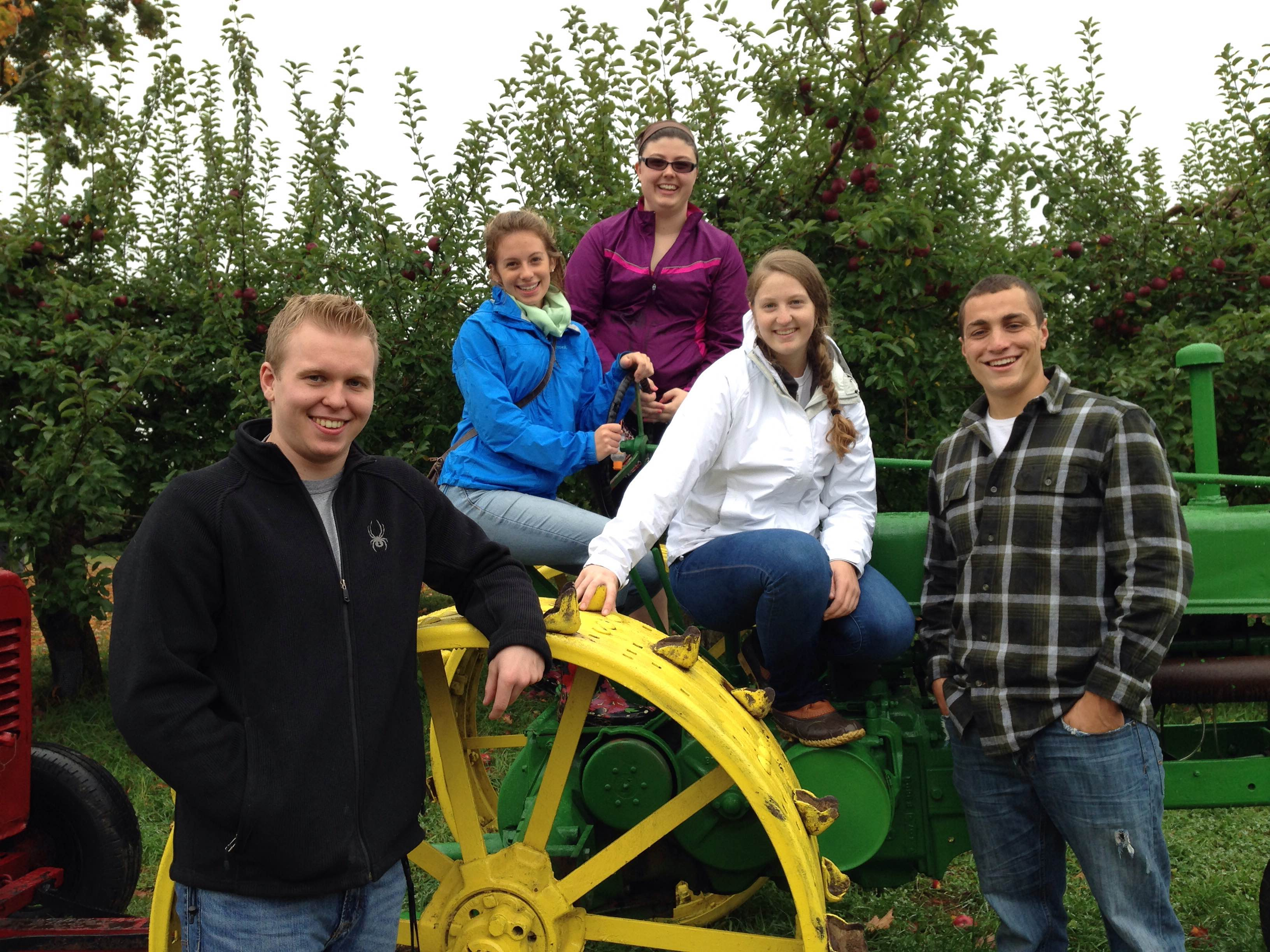 Students sitting on a tractor in an apple orchard.