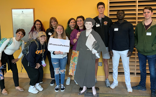 Students posing with a cutout of Frances Perkins after attending an event together.