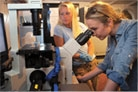 image of student and faculty using a microscope