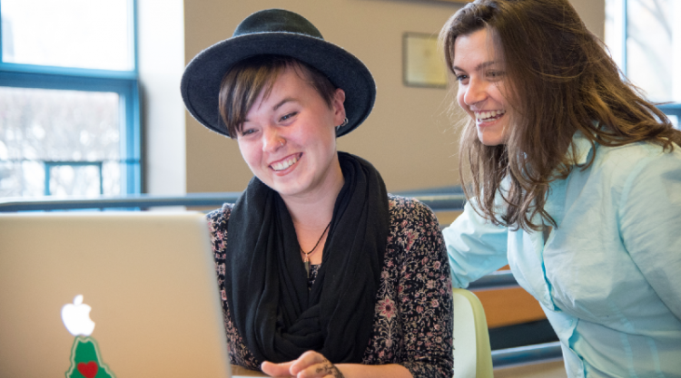 Two students smile while looking at an open laptop. One student is seated and wearing a black hat with a brim; the other is standing and wearing a light aqua shirt.  The laptop has a green sticker on it in the shape of the state of Maine with a red heart inside it.