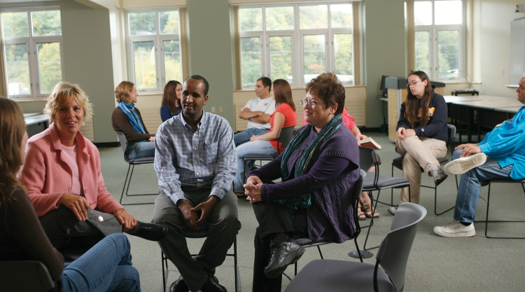 Groups of men and women sitting in circles and talking