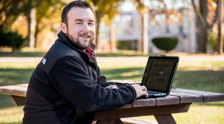 Man smiling and working on laptop