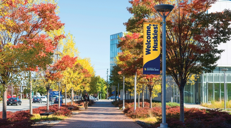 A student walking up Bedford Street on a sunny autumn day. A lamppost bears a banner that reads 'Welcome Huskies' above the USM logo.