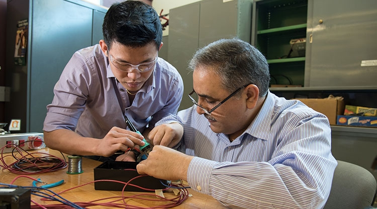 A University of Southern Maine student and faculty member work together on an electrical engineering project.