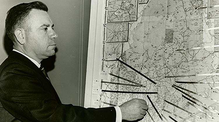 A professor points to a map.