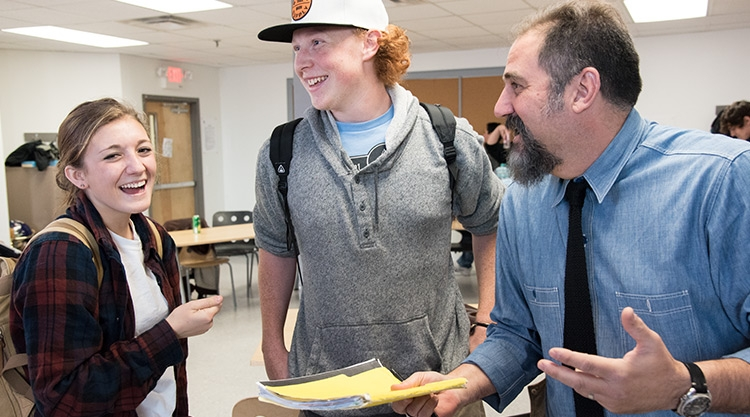A University of Southern Maine graduate student talks with high school students.