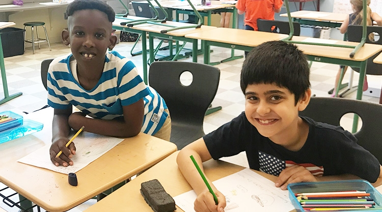 Two students sit at desks with paper and pencils.
