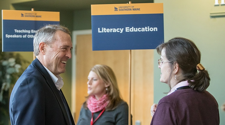 """University of Southern Maine graduate faculty talk to each other in front of a """"Literacy Education"""" sign."""
