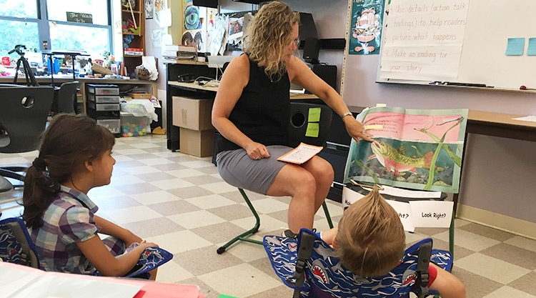 A University of Southern Maine graduate student reads a book to K-8 students.