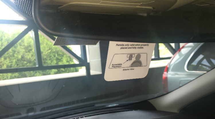A parking permit hangtag that is placed around a rearview mirror of a vehicle.