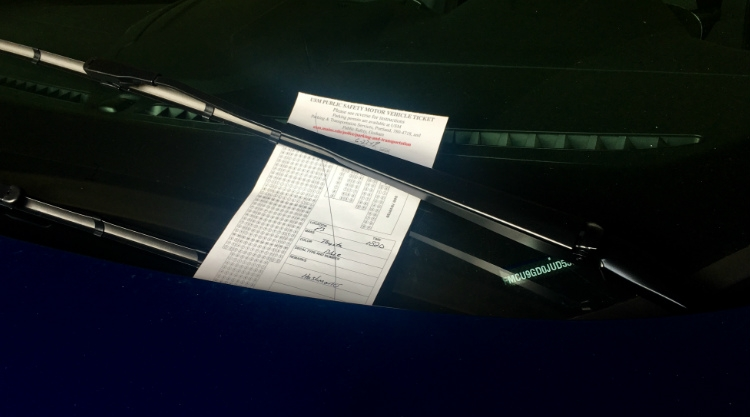 A parking ticket on the windshield of a vehicle.
