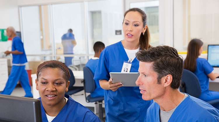 Two nurses site at a table, a woman is looking at a computer. Another nurse stands behind them, holding a clipboard.