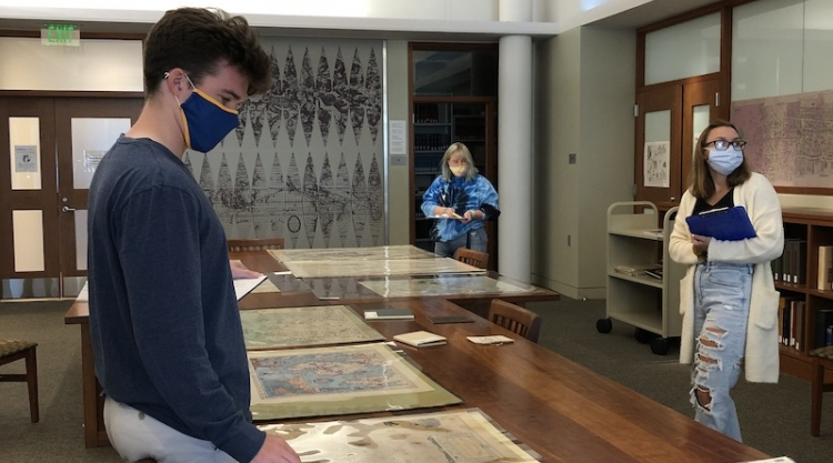 Three students wearing masks look at maps, at the Osher Map Library.