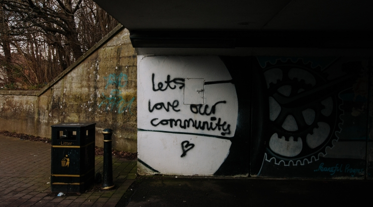 """Black graffiti under a bridge on a white pillar. The graffiti says """"Lets Love Our Community"""" with a roughly drawn heart below the text."""