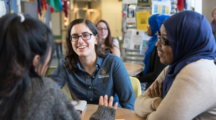 Three diverse women hang out at a table in Woodbury Campus Center