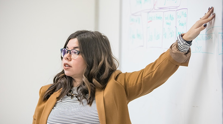 Teacher pointing to notes on a whiteboard.