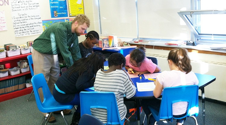 Teacher working with a group of elementary students who are seated at a table in a classroom.