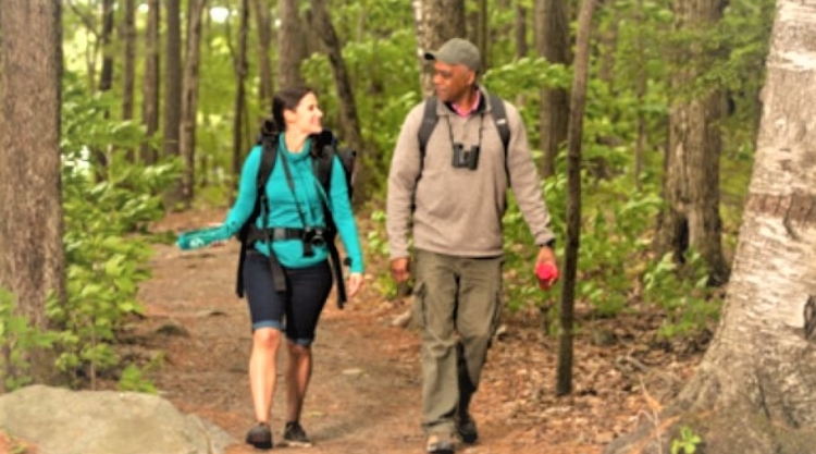 White woman and black man walking in forest.