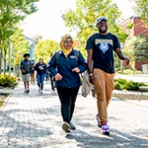 Students outside on a sunny autumn day, walking down Bedford Street on our Portland campus. Several are wearing clothing featuring the USM logo.