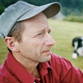 Rick Bass in a red shirt and gray hat with dog in background