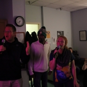 Three ROCC student peers singing at Karaoke
