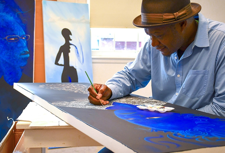 Daniel Minter working on a painting during his time as a USM artist-in-residence