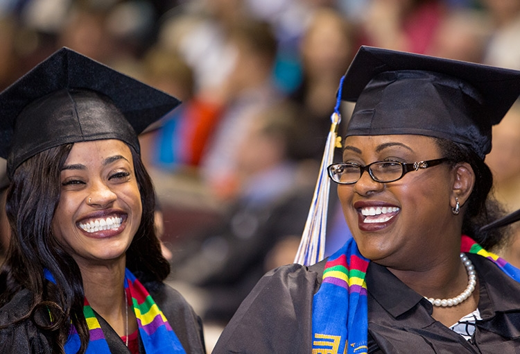 Two smiling adult female students at Commencement