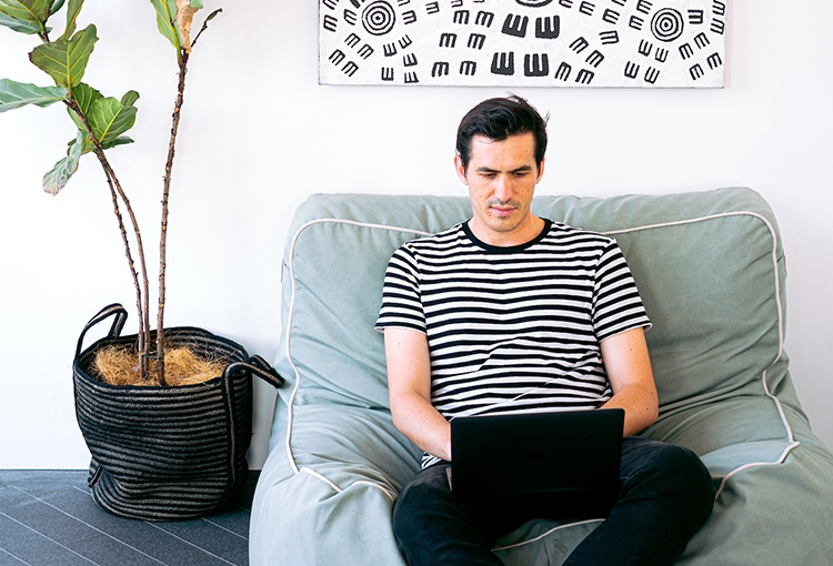 Man sitting in a chair, next to a plant, with laptop on lap.