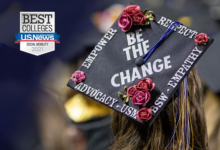 A badge that reads, 'Best Colleges U.S. News & World Report Social Mobility 2021' appears in the upper left corner of a photo of a graduate wearing a mortarboard decorated with small, fake roses and text that reads, 'Be the change; empower; respect; advocacy; empathy; USM BSW.' A tassel with blue, gold, and white strands hangs over one edge.