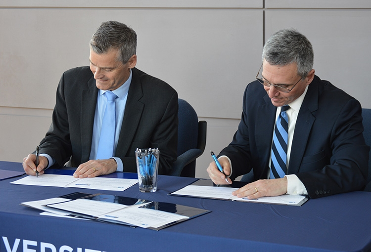 Photo of USM President Glenn Cummings (left) and Southern Maine Community College President Ron Cantor (Right) signing new agreements to allow SMCC engineering students enroll at USM after 2 years
