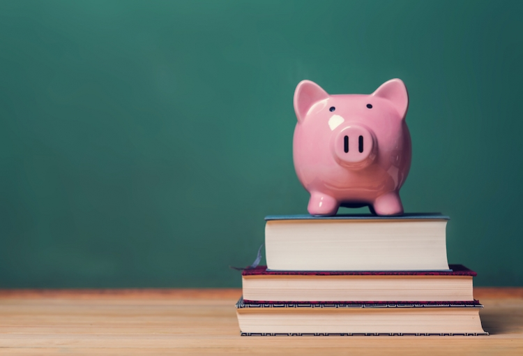 A piggybank sits on a stack of three books