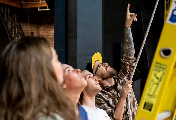 Three students looking up a ladder, following the sightline created by a professor's tattooed arm pointing out something in the stage rafters attached to the rope he is holding.