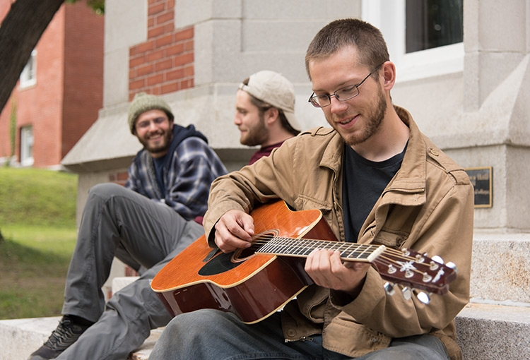 Three students sitting on the steps of one of our residence halls. The student closest to the camera is playing an acoustic guitar.