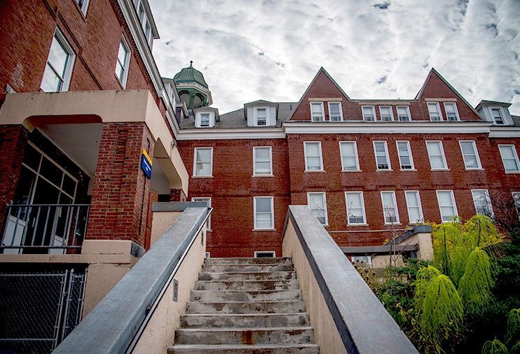 A view from the bottom of a staircase leading to one of the entrances to Robie-Andrews Hall
