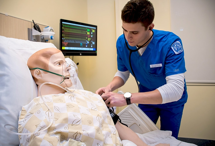 A student taking the vitals of a mannequin in our nursing simulation lab